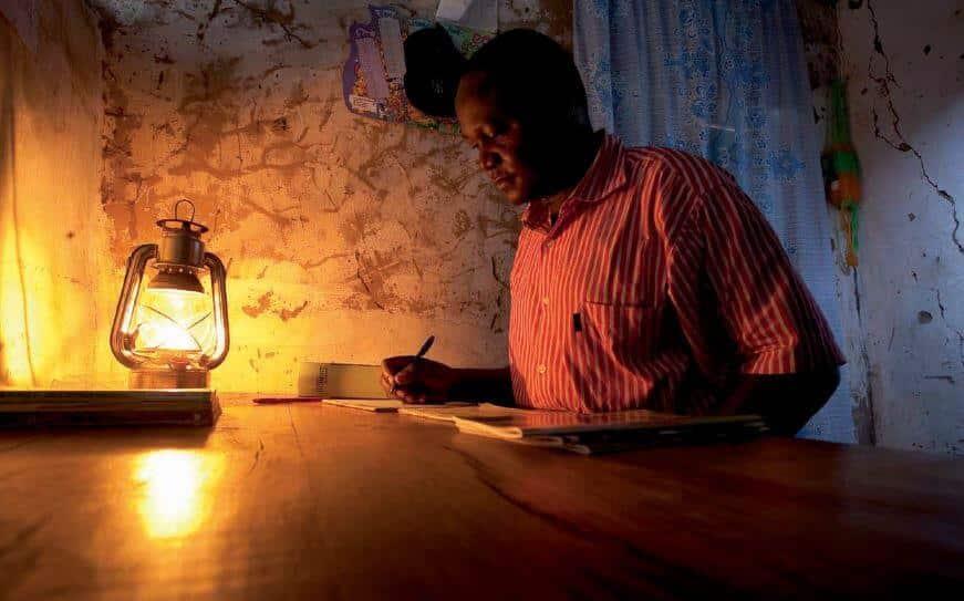 Homme travaillant avec une lampe à pétrole