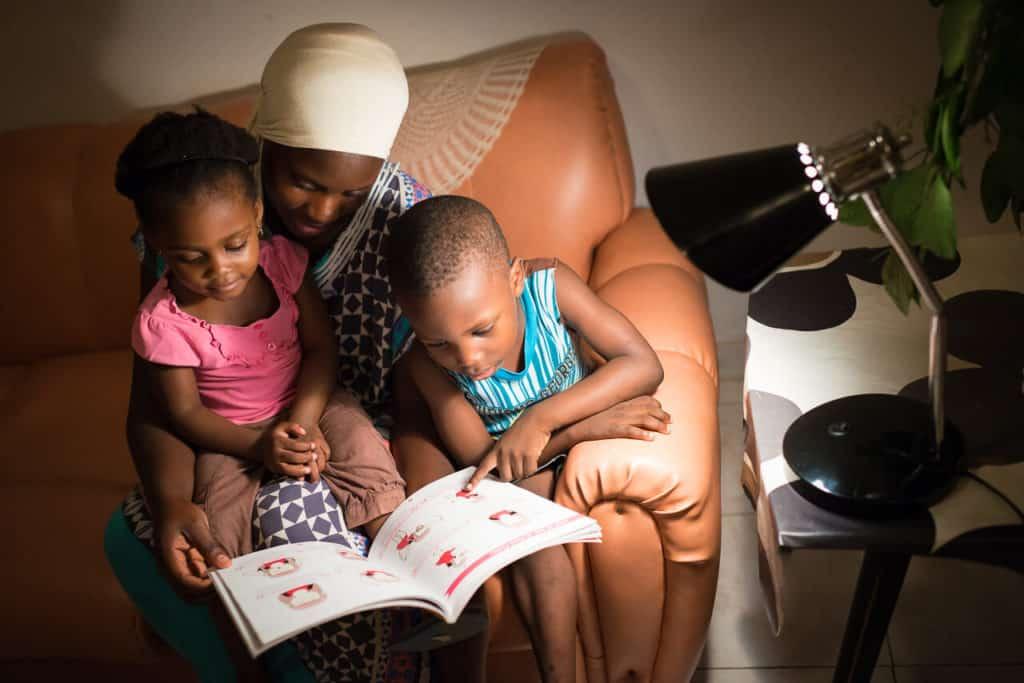 Jeune femme aidant ses enfants à faire leurs devoirs à la maison
