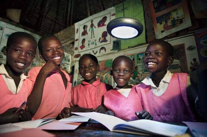 Groupe d'élèves faisant leurs devoir et éclairés par énergie solaire